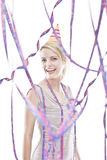 Young attractive blonde teenager celebrating. Young attractive blonde teenager partying behind paper streamer Royalty Free Stock Photo