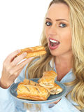 Young Attractive Blonde Woman Holding and Eating Saugage Rolls Royalty Free Stock Photography