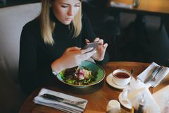 Young attractive blonde woman uses phone at dinner in restaurant. Lifestyle and food royalty free stock images
