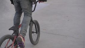 BMX rider outdoors. Young attractive boy rides his red bmx bike in park outdoors on a sunny summer day in slow motion. Active and healthy lifestyle concept stock video