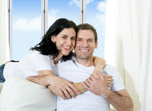 Young attractive Brazilian couple with woman hugging his husband in couch Stock Image