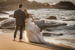 Young attractive bridal couple on beach with wine Stock Photography