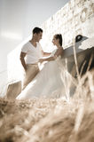 Young attractive bridal couple flirting outdoors Stock Photos