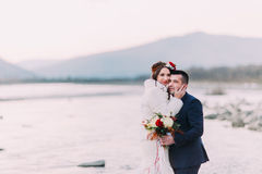 Young attractive bridal couple posing on pebble beach near the mountain river Royalty Free Stock Photos