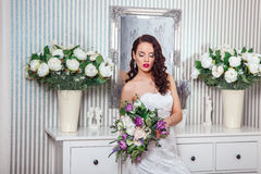 Young attractive bride with flowers indoors . Bride`s morning. Happy Bride waiting groom. Royalty Free Stock Photography