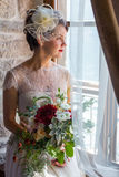 Young and attractive bride sitting by the window Stock Image