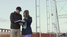 Young people discuss the book at the bridge stock footage