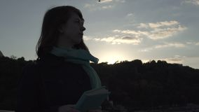 Young lady reads the book during the sunset. Young attractive brown-haired girl is outdoors. Beautiful lady holds the book in her hands and reads it with stock video footage