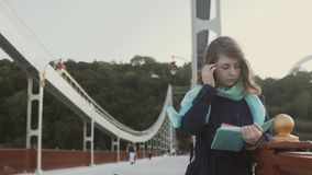 Young girl read book on the bridge stock footage