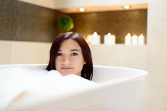 Young attractive brunette in bubble bath. Royalty Free Stock Photo