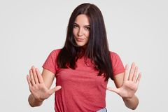Young attractive brunette female makes stop gesture, has serious expression, denies doing something, has long straight dark hair,. Wears pink t shirt, poses stock photography