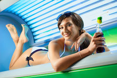 Young attractive brunette girl is laying in the working solarium Royalty Free Stock Image