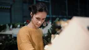 Young attractive brunette girl at the store chooses an artificial Christmas tree and toys, Christmas decoration. Royalty Free Stock Photos