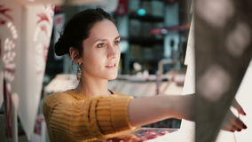 Young attractive brunette girl at the store chooses lamps, Christmas decor. Royalty Free Stock Photography