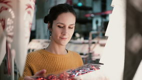 Young attractive brunette girl at the store chooses lamps, Christmas decor. Stock Photo