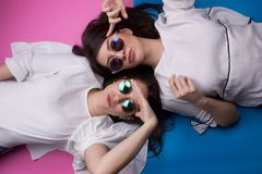 Young girls having fun. Young attractive brunette girls with sunglasses having fun isolated background Royalty Free Stock Photo