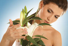 A young and attractive brunette with a lily Stock Images