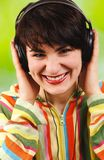 Young attractive brunette listens to music. Royalty Free Stock Images