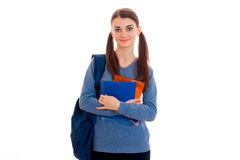 Young attractive brunette student woman with blue backpack on her shoulder and folder for notebooks in hands looking at Stock Images