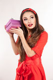 Young attractive brunette woman holding christmas gift. Royalty Free Stock Photo