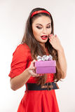 Young attractive brunette woman holding christmas gift. Royalty Free Stock Photography