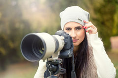 Young attractive brunette woman holding the retro camera in outdoors. Beautiful young girl shooting with professional camera Royalty Free Stock Photo