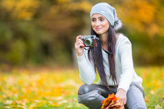 Young attractive brunette woman holding the retro camera in outdoors. Beautiful young girl shooting with retro camera in the autum Royalty Free Stock Photos