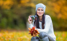 Young attractive brunette woman holding the retro camera in outdoors. Beautiful young girl shooting with retro camera in the autum Stock Image