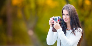 Young attractive brunette woman holding the retro camera in outdoors. Beautiful young girl shooting with retro camera in the autum Stock Photos