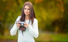 Young attractive brunette woman holding the retro camera in outdoors. Beautiful young girl shooting with retro camera in the autum Royalty Free Stock Photography