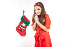Young attractive brunette woman looking into christmas stocking. Royalty Free Stock Photography