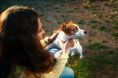 Young attractive brunette woman playing with her dog in green park at summer, lifestyle people concept. Young beautiful woman holds a hand over the pet dog`s paw Stock Photo