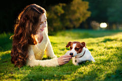 Young attractive brunette woman playing with her dog in green park at summer, lifestyle people concept. Outdoor portrait of beautiful girl and the pet dog Jack Stock Image