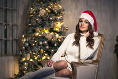 Young attractive brunette woman in Santa hat near Christmas tree Stock Photography