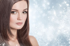 Young attractive brunette woman in a snow. Winter beauty concept Stock Photos