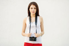 Young attractive brunette woman in white t-shirt posing with a photo camera Stock Photos
