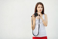 Young attractive brunette woman in white t-shirt posing with a photo camera Royalty Free Stock Image