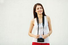 Young attractive brunette woman in white t-shirt posing with a photo camera Stock Image