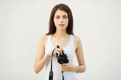 Young attractive brunette woman in white t-shirt posing with a photo camera Royalty Free Stock Photos