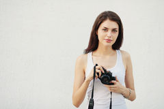 Young attractive brunette woman in white t-shirt posing with a photo camera Stock Photography