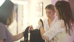Young attractive brunette women helping blond hairdresser stylist make salon hairstyle on model with black straight hair. Young attractive brunette women helping stock footage