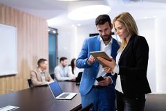 Attractive business couple using tablet in their company. Young attractive business couple using tablet in their company Stock Photo