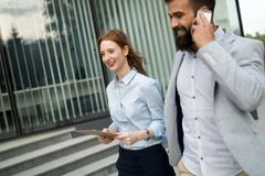 Young business couple walking outdoor near office building. Young attractive business couple walking outdoor near office building royalty free stock image