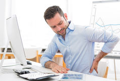 Young attractive business got backache because of burn out Royalty Free Stock Images