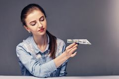 Young attractive business lady launches a money plane royalty free stock photo