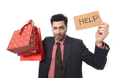 Young attractive business man in stress holding lot of shopping bags and help sign looking tired bored and worried Royalty Free Stock Photos