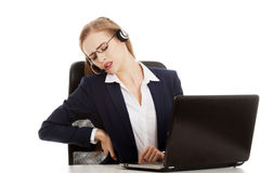 Young attractive business woman at call center is having backach Royalty Free Stock Image