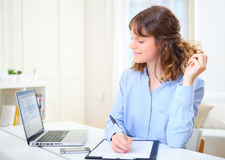 Young attractive business woman copying data on paper. View of a young attractive business woman copying data on paper Stock Image