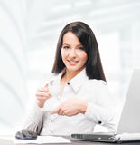 Young and attractive business woman drinking coffee in the office Stock Image