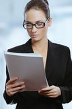 Young attractive business woman in glasses reading contract documents Royalty Free Stock Photo